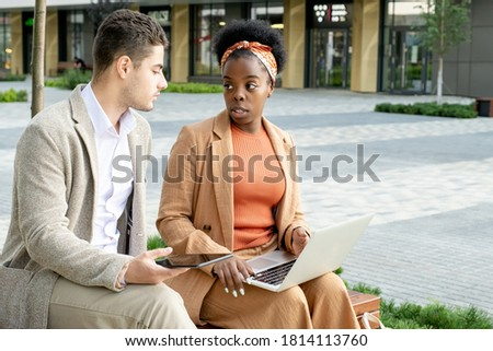 Young serious businessman with digital tablet listening to his African female colleague making presentation and asking for advice stock photo