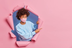 Young serious curly haired woman wears protective face mask against coronavirus or contagious disease dressed in casual jumper stands in ripped hole indicates at blank space on pink background