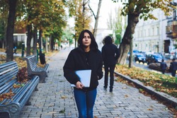 Young serious ethnic female in casual outfit with hand in pocket looking at camera while walking on street and carrying laptop