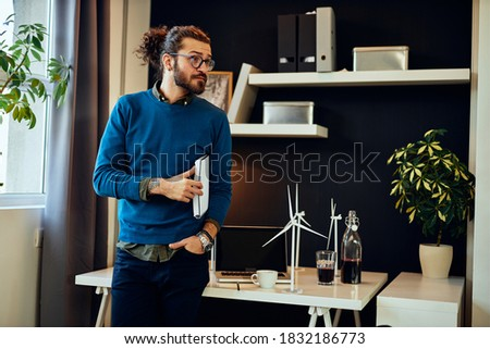 Young serious handsome hipster standing in his office, holding documents under armpit and preparing for important meeting with his boss. Sustainable development concept. Stock foto ©
