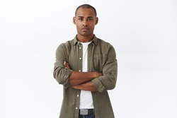Young serious-looking, confident african american male employee, cross hands chest, waiting for appointment, apply for job position, look determined, standing white background