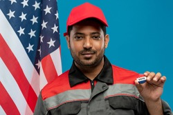 Young serious repairman of Hispanic ethnicity holding vote insignia against stars-and-stripes flag while standing in front of camera