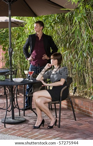 Young serious romantic couple dining together on patio