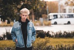 Young serious teen boy 15-16 year old wearing denim jacket and hoodie posing over city street background closeup. Looking at camera. Teenagerhood.