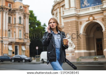 Young serious woman in leather jacket and jeans thoughtfully looking iaside holding cup of coffee to go in hand talking on cellphone on cozy city street