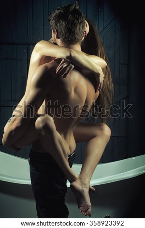 Young sexual passionale sensual couple of attractive flexible woman with beautiful naked body embracing handsome muscular man in jeans with legs in bathroom on wood backdrop, vertical photo