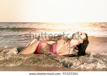 Young sexy and fit woman posing on the beach in Greece