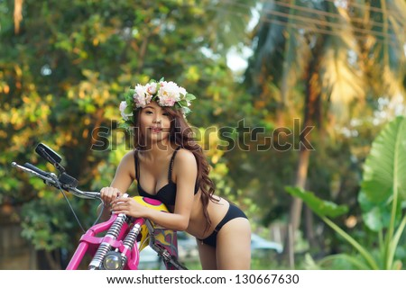 Young sexy Asian woman in black lingerie on pink motorcycle.