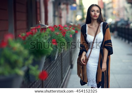 Young sexy beautiful pretty woman in white elegant dress and cape walking at city street with handbag. Fashion portrait of stylish trendy girl with shallow DOF #454152325