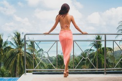 young  sexy beautiful woman in pink bikini, posing on terrace of resort hotel, slim, tanned skin, fashion glamour accessories, relaxed, sensual, summer vacation, view from back