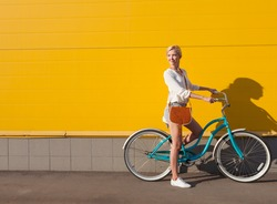 Young sexy blonde girl is standing near the vintage green bicycle with brown vintage bag