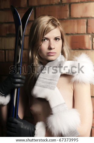 Young sexy blonde with skis. Mountain-skier.Studio. Brick background.