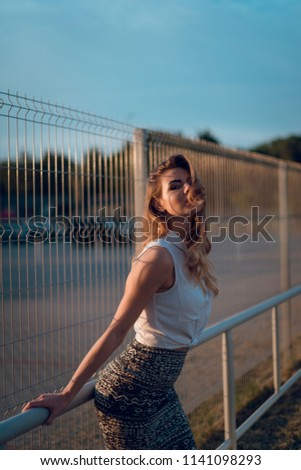 Young sexy blonde woman in white blose and skirt posing near the wire fence on parking area on sunset. Urban concept #1141098293