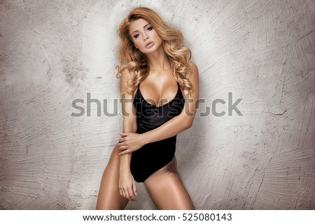 Young sexy blonde woman posing in fashionable swimsuit. Girl with ideal body. Studio shot.
