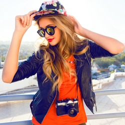 Young sexy blonde woman posing in the roof, wearing leater jacket, swag floral hat mirrored sunglasses and bright make up, holding vintage camera, Lifestyle portrait bright toned colors.