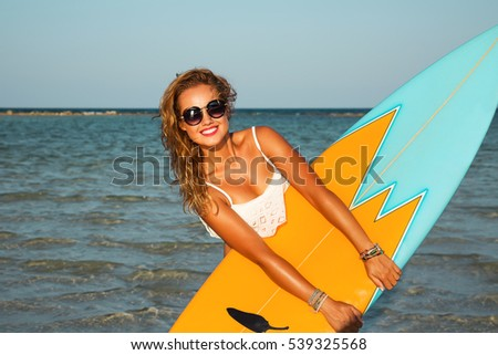 Stock Photo Young sexy blonde woman with long curly hairs and sportive tanned body. Smiling and posing with surf board near blue ocean in sunny summer day. Wearing stylish round sunglasses. Ready for surfing