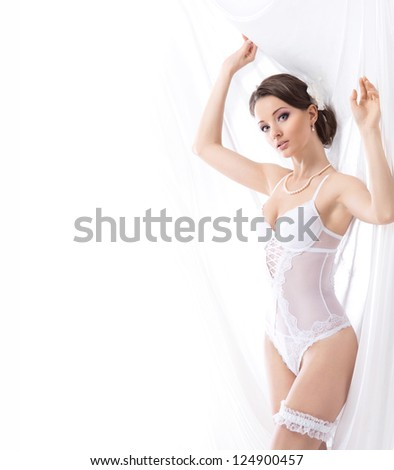 Young sexy bride in erotic lingerie over white background with some blank space