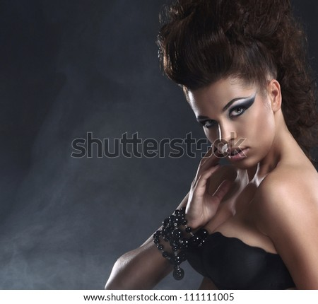 Young sexy brunette over black background with smoke
