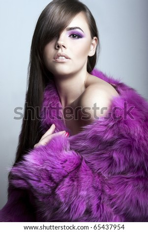 Young sexy brunette wearing a bright pink fut coat