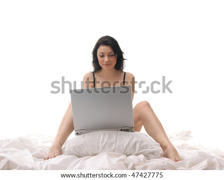 Young sexy brunette working witch laptop in the bed