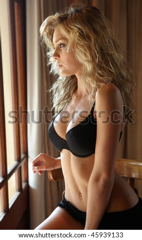 Young sexy Caucasian adult woman in lingerie in a bedroom setting. next to a window on a high chair with sunlight shining through the windows