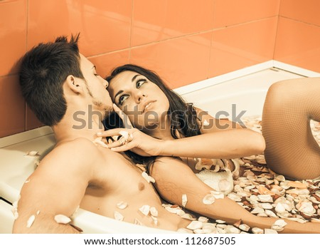 young sexy couple enjoy each other in bathroom of roses