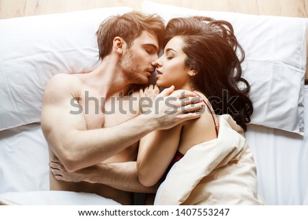 Young sexy couple have intimacy on bed. Lying in sleeping pose. Embrace each other. Kissing. Passionate couple together in bed. White background. Daylight. Beautiful people.