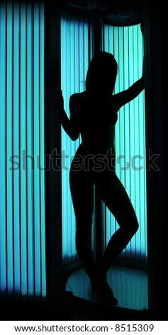 Young sexy female in a tanning cabin, shoot for shape against a light - full body length version.
