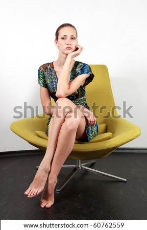 Young sexy female posing in the fashionable chair looking at camera