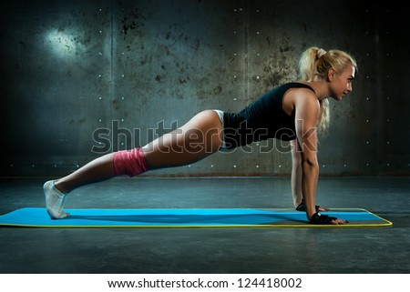 Young sexy fitness woman doing push-ups.