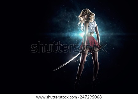 Stock Photo Young sexy girl is standing with the swords in th dark spotlight