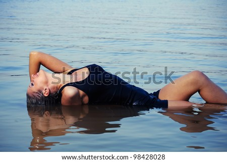 Young sexy girl posing in the water - stock photo