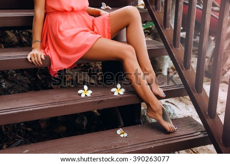 Young sexy girl wear summer peach dress,tropical flowers,long toned legs,cosmetology,sugar waxing,tan skin body,bright toned colors.Young pretty brunette woman,wearing bright clothes,outdoor fashion