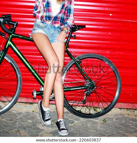 Young sexy girl with long nice legs posing with sport style cyclocross bicycle on red background urban style night flash picture