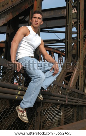 Young sexy man in a white tank top sitting on the metal construction