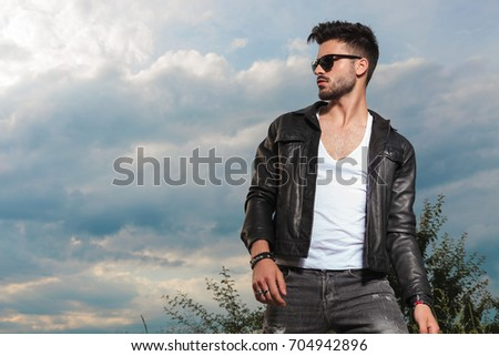 young sexy man in leather jacket and sunglasses standing outdoor against cloudy sky #704942896