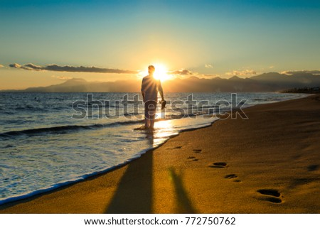 Young, sexy man is walking at the beach into a beautiful sunset, holding his flip flops in his hand - wonderful Landscape, blue water/sea - take a picture of holiday