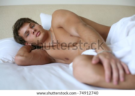 Young sexy man lying on a bed - stock photo