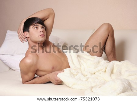 Young sexy man lying on a bed.