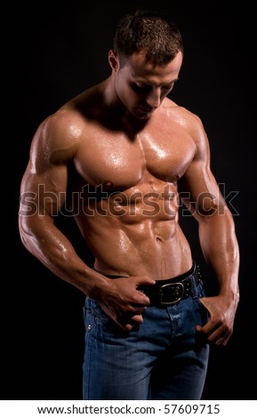 Young sexy man with muscular body on black.