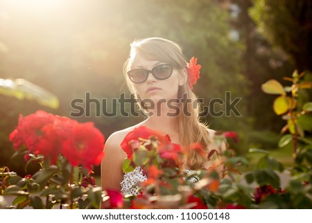young sexy model in flower garden smelling red roses