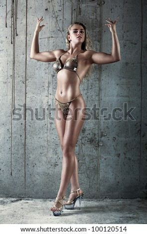 Young sexy muscular woman on wall background. - stock photo