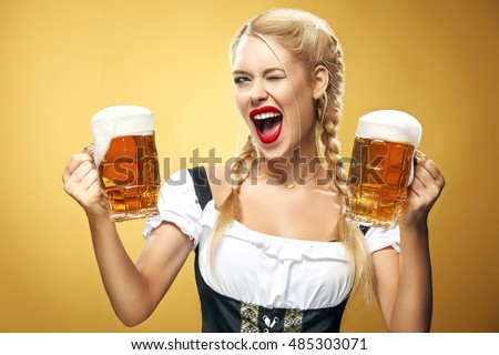 Young sexy Oktoberfest waitress, wearing a traditional Bavarian dress, serving big beer mugs on blue background. #485303071