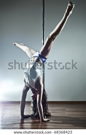 Young sexy pole dance woman. On wall background.