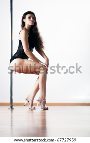 Young sexy pole dance woman. On white wall background.