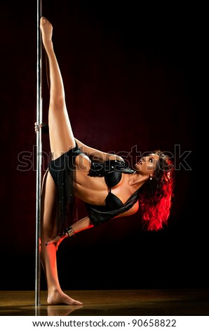 Young sexy pole dance woman. Red lights.