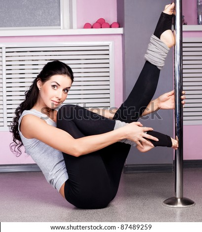 Young sexy pole dance woman, wearing sports clothes