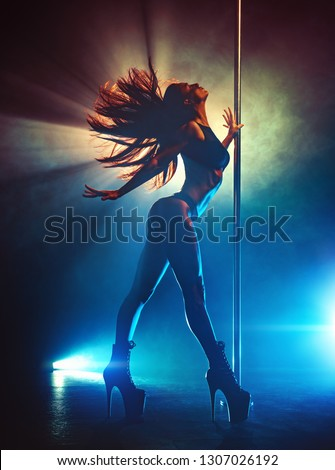 Young sexy slim brunette pole dancing woman shaking hair. Silhouette with smoke and lights.