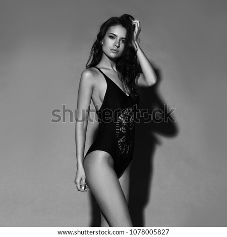 4226e15fcf Young sexy slim tanned woman in black swimsuit posing against gray  background. Full length fashion · Portrait of beautiful ...