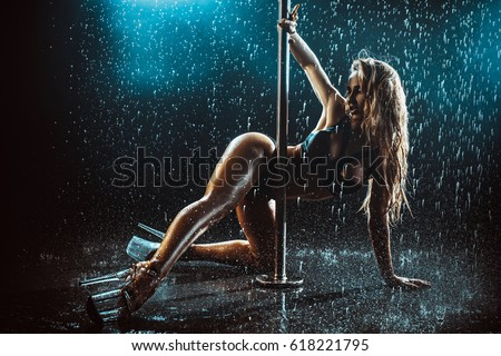Young sexy slim woman pole dancing with water rain drops